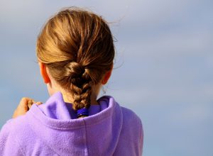 A child wearing a hoodie. Should schools introduce hoodies and tracksuit bottoms as uniform?