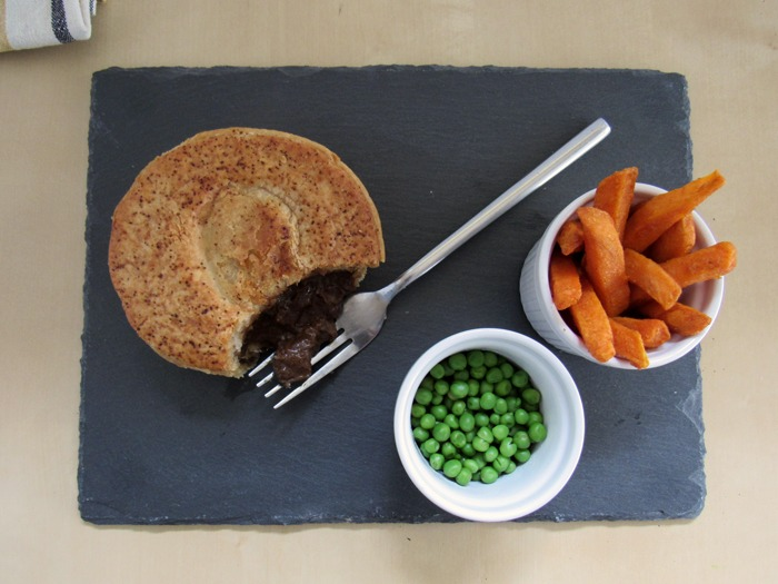 A pie with sweet potato fries and peas.