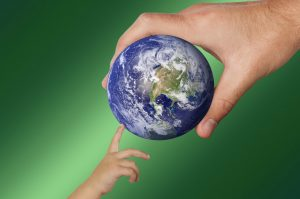 A concept image showing an adult handing the world to a child.