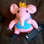 A Clangers toy holding a remote control.