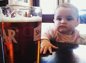 A baby looking at a pint of beer.