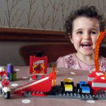 A happy little girl with a LEGO Toy Story 4 playset.