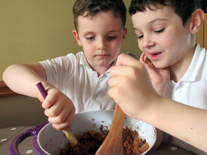 Two young boys mixing ingredients in a bowl.