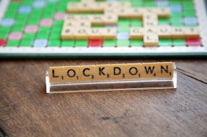 A Scrabble set with the word 'lockdown' created with the tiles.