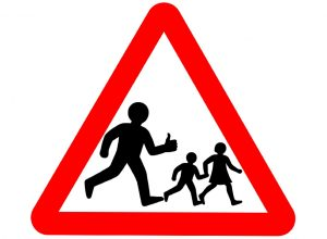 A UK school sign edited to include a parent giving a thumbs up as they love the school run.