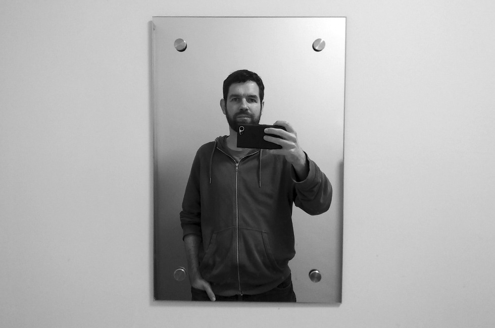 A man taking a selfie in a mirror.