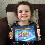 A toddler holding a tablet displaying the Matific Galaxy title screen.