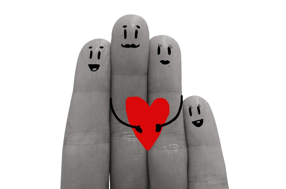 Four fingers with faces drawn on them to depict a family. The father and the mother are in the middle, holding a heart.