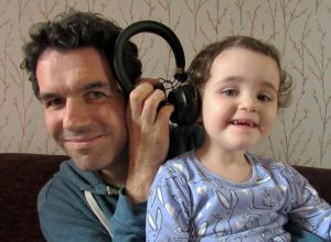 A father and daughter sharing a pair of headphones. Should we be making sure children have good taste in music?