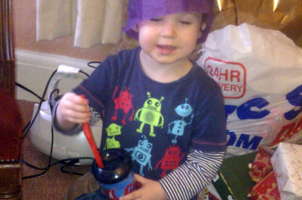 A child wearing a Christmas cracker hat.