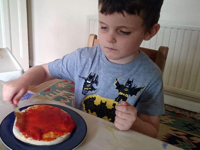 A young boy making pizza.