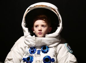 A child in an adult's spacesuit.