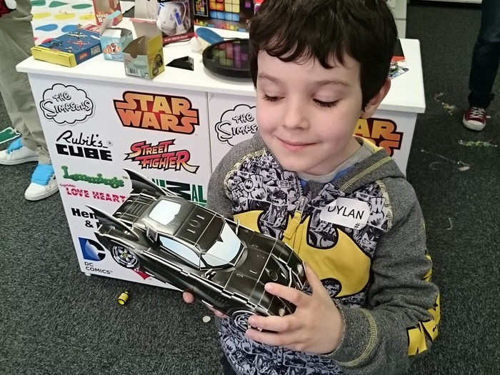 A happy child with a model Batmobile.