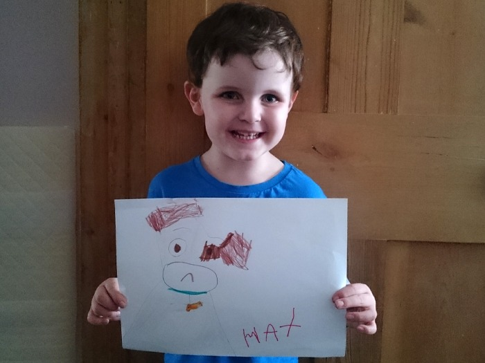A boy proudly holding his drawing of a dog.