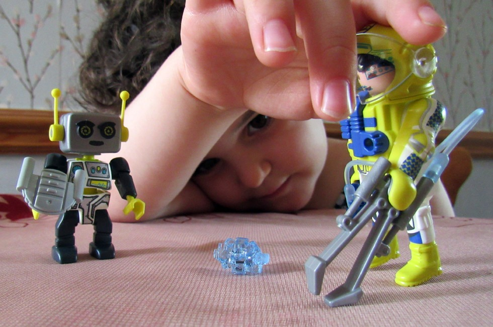 A child playing with some PLAYMOBIL figures.