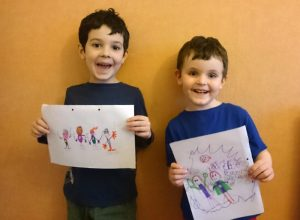 Two young boys proudly showing their drawings of super heroes.