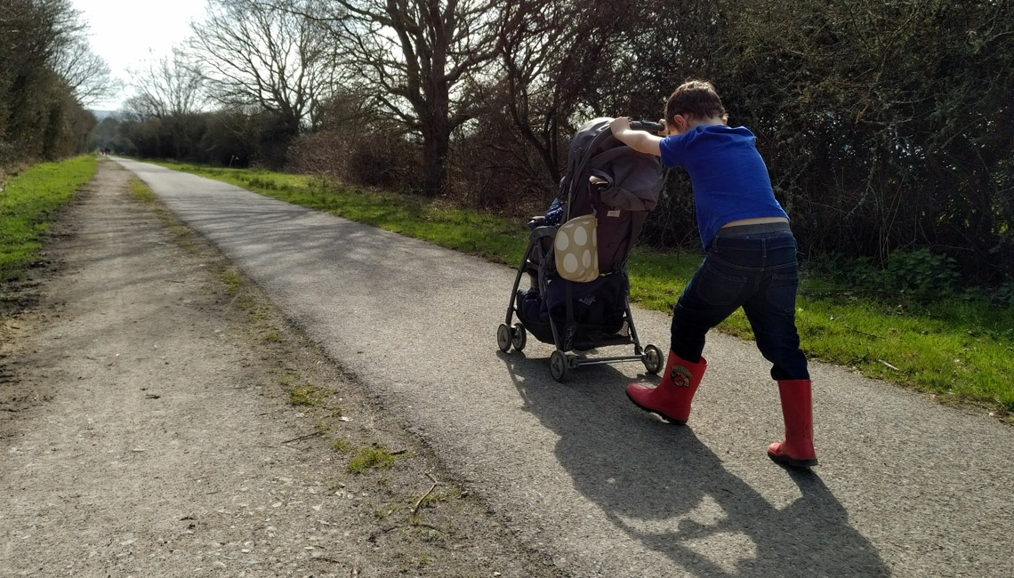 A child pushing a younger sibling in their pushchair.