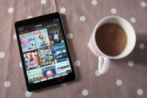 A tablet running the Readly app and a cup of tea.