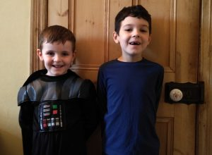 Two boys stood in front of an interior door.