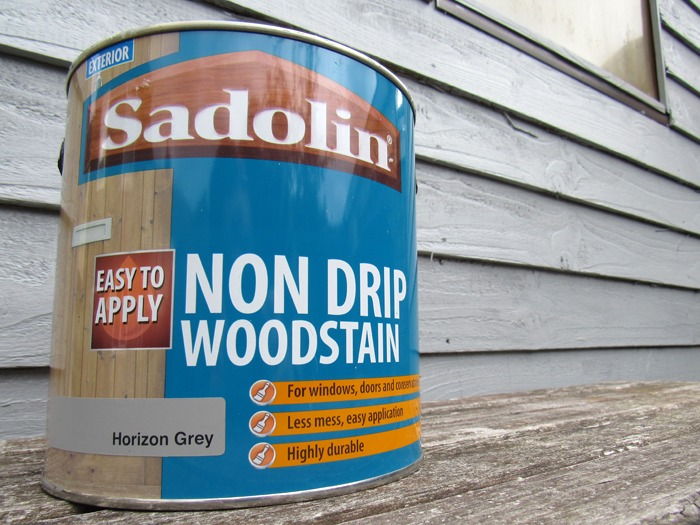 A tin of Sadolin non drip woodstain in front of a newly painted shed.