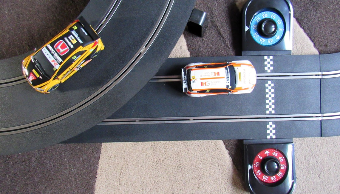 Two cars racing on the Scalextric Touring Car Battle set.