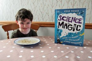 A child with a copy of Science is Magic.