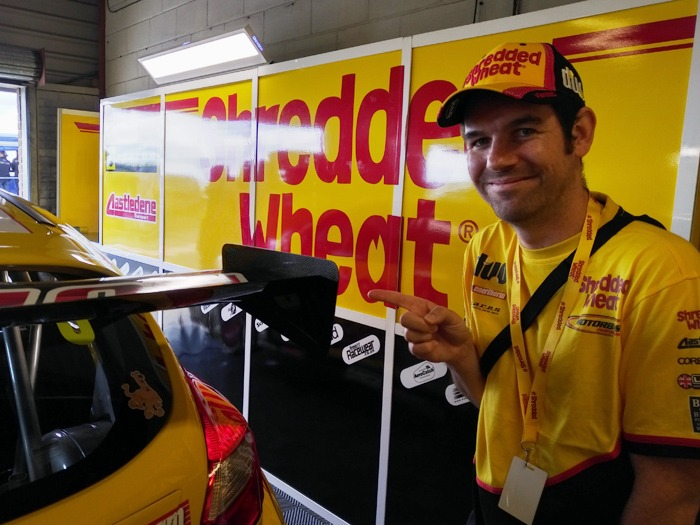 A man wearing Shredded Wheat branded clothing pointing at the spoiler of a car.