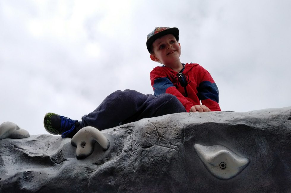 A young boy wearing a Spider-man hoodie sat on top of a climbing wall.