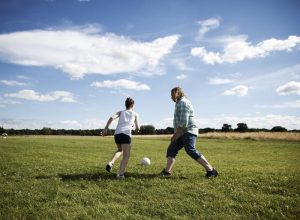 A father and daughter playing football in the park.