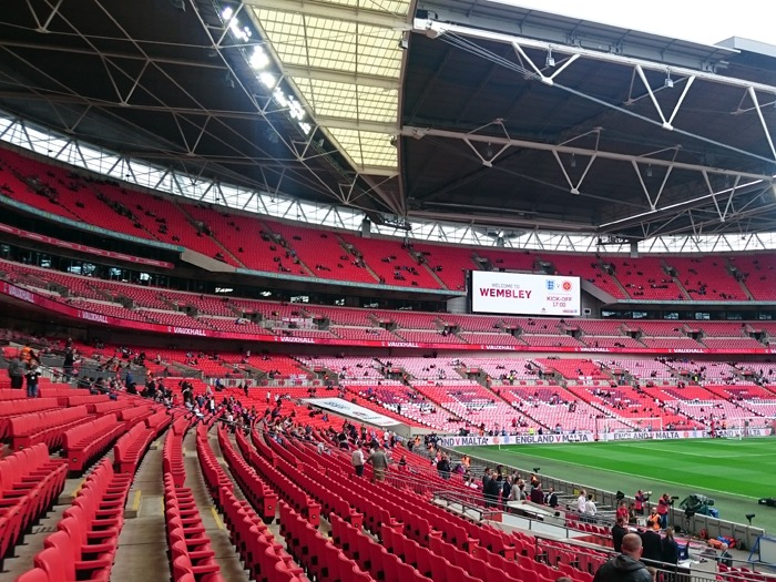 The inside of Wembley Stadium showing the famous red seats.