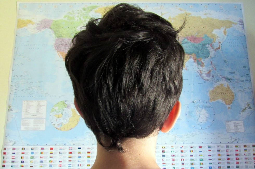 A young boy looking at a world map. A proper little man of the world!