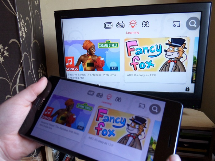 A child holding a smartphone with the YouTube Kids app running and a television in the background. Both devices are showing the same content.