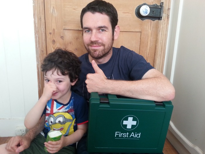 A man and his son with a first aid kit. The son is holding his nose.